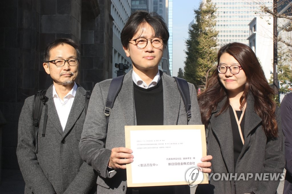 This photo, taken on Dec. 4, 2018, shows a Japanese activist and two South Korean lawyers representing the four victims of Japan's wartime forced labor showing a document calling on Nippon Steel & Sumitomo Metal Corp. to carry out the top court's order to compensate the victims before visiting the headquarters of the Japanese firm in Tokyo. (Yonhap)