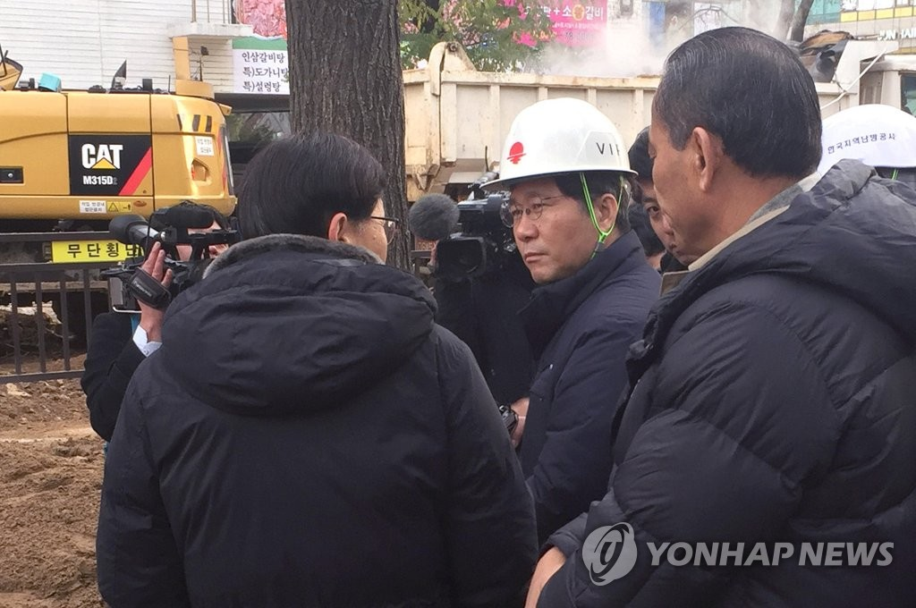 Sung Yun-mo (2nd from L), minister of trade, industry and energy, is briefed on a plumbing accident in Goyang, north of Seoul, on Dec. 5, 2018, after a heating pipe burst the previous evening, claiming one life and wounding several others, in this photo provided by the ministry. (Yonhap)