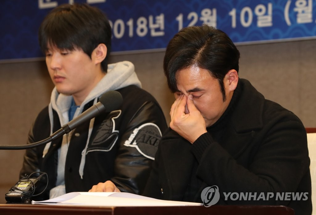 In this file photo from Dec. 10, 2018, Moon Woo-ram (R), former outfielder of the Nexen Heroes, wipes away tears during a press conference, in Seoul, where he claimed he was wrongfully convicted of match fixing. (Yonhap)