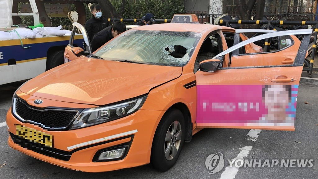 Police officers investigate a taxi owned by a driver identified only as 57-year-old with the surname Choi, on Dec. 10, 2018, after the driver died after setting himself on fire in protest of Kakao Corp.'s carpool service. (Yonhap)