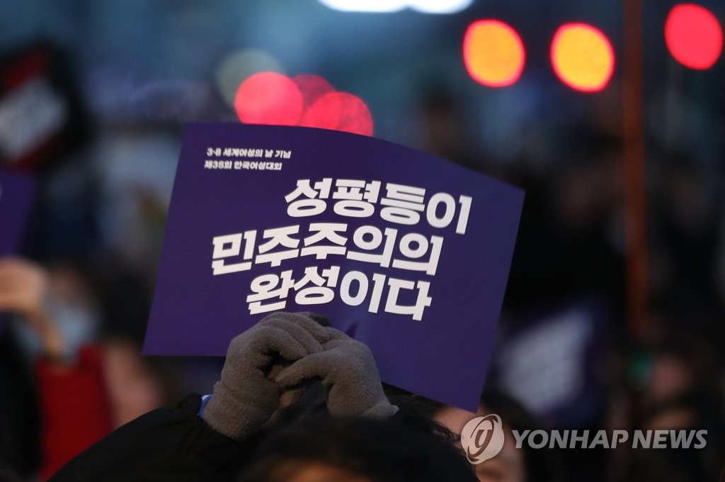 "This photo taken on March 8, 2019, in Seoul shows a person attending a Women's Day ceremony holding a sign that reads, ""Gender equality completes democracy."" (Yonhap)"