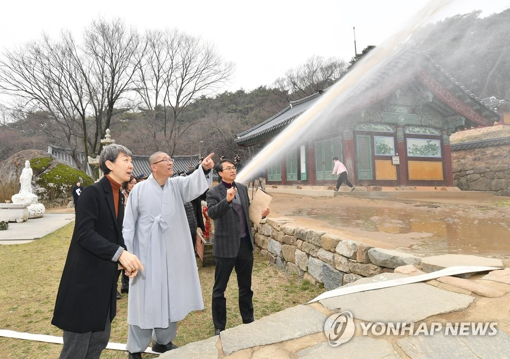 This file photo provided by the Cultural Heritage Administration (CHA) shows CHA chief Chung Jae-suk (L) observing an inspection of fire safety equipment at Sudeok Temple in Yesan, South Chungcheong Province, on March 12, 2019. (PHOTO NOT FOR SALE) (Yonhap)