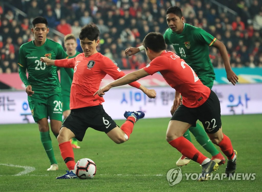 Hwang In-beom of South Korea (2nd from L) takes a shot against Bolivia in a men's friendly football match at Munsu Football Stadium in Ulsan, 400 kilometers southeast of Seoul, on March 22, 2019. (Yonhap)