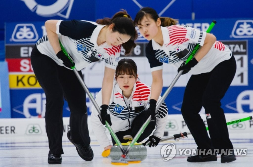 In this March 24, 2019, file photo provided by the World Curling Federation, members of the South Korean women's team are in action against Switzerland in the semifinals of the World Women's Curling Championship at Silkeborg Sportscenter in Silkeborg, Denmark. From left are Yang Tae-i, Kim Hye-rin and Kim Su-jin. (PHOTO NOT FOR SALE) (Yonhap)