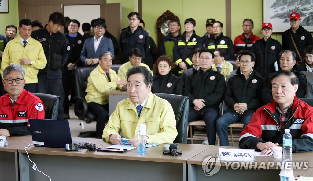 Prime Minister Lee Nak-yon is briefed by officials on the blaze in the control center set up in a community facility in Goseong, Gangwon Province, on April 5, 2019. (Yonhap)