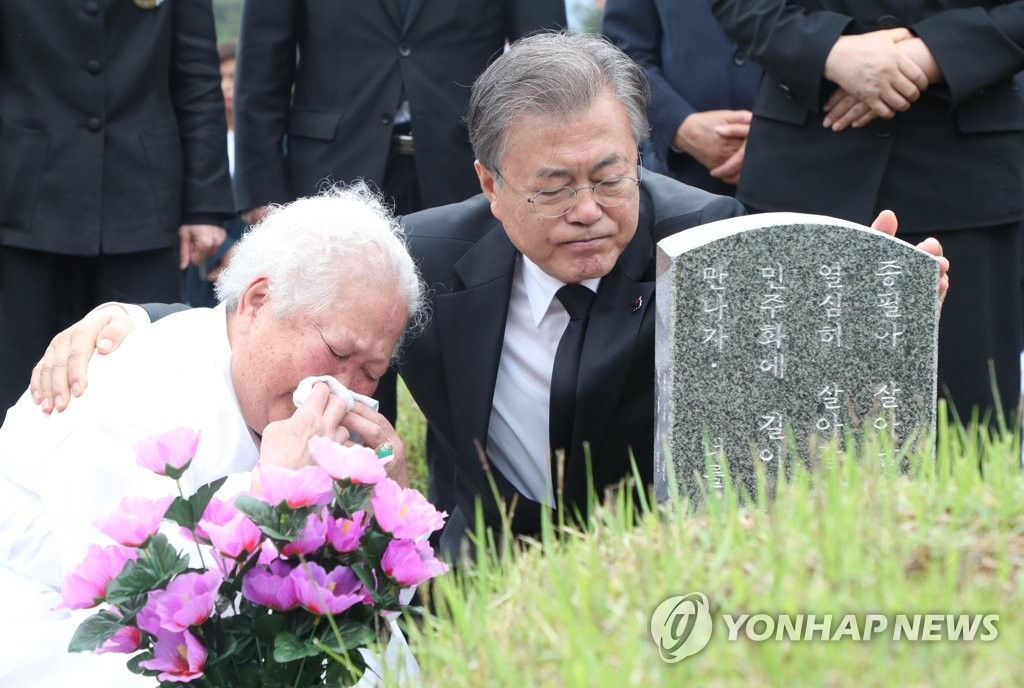 President Moon Jae-in (R) consoles a bereaved family member of a victim of the 1980 civilian massacre committed by a military junta during the May 18 Democratization Movement in Gwangju while visiting a national cemetery there on May 18, 2019. (Yonhap)