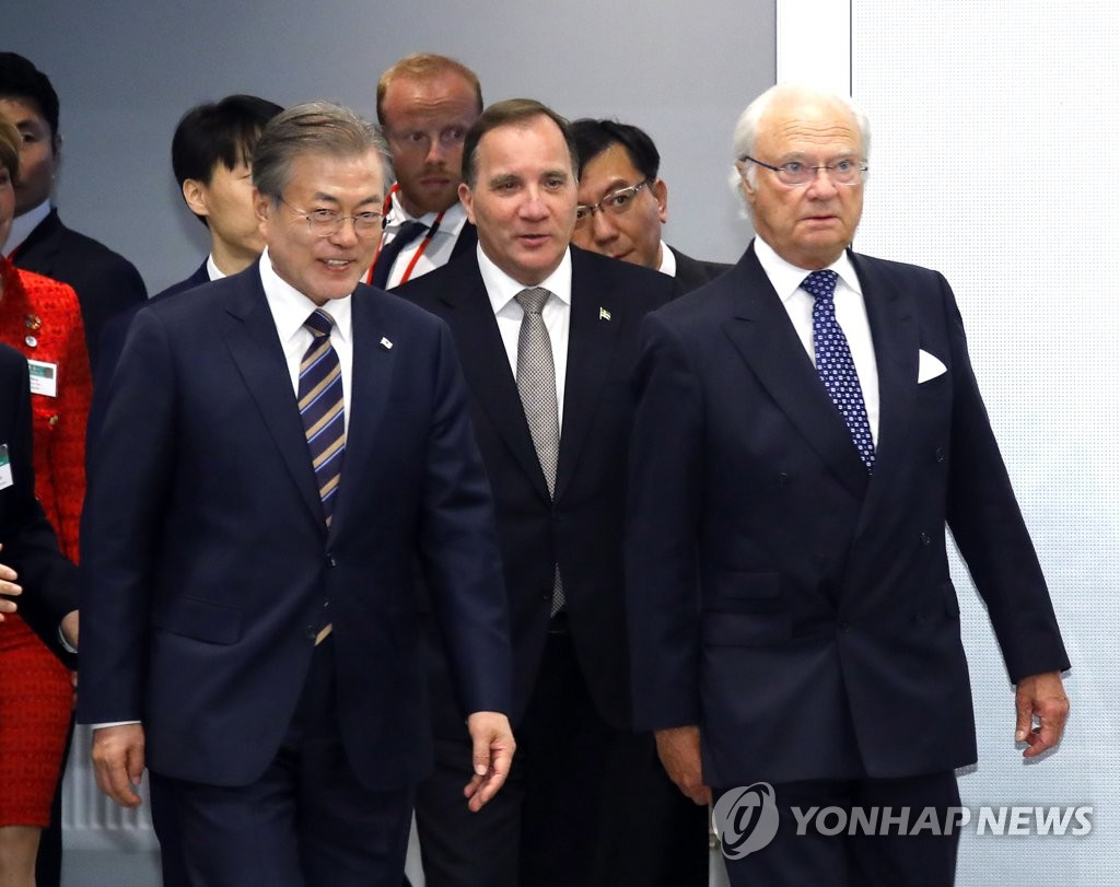 President Moon Jae-in (L) enters the venue for the South Korea-Sweden Business Summit at a downtown hotel in Stockholm on June 14, 2019, along with King Carl XVI Gustaf (R) and Prime Minister Stefan Lofven (C).