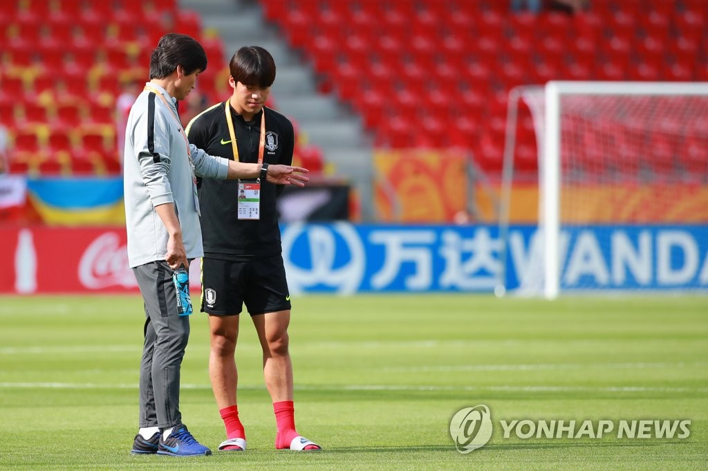 South Korea head coach Chung Jung-yong (L) speaks to his defender Lee Kyu-hyuk before the FIFA U-20 World Cup final against Ukraine at Lodz Stadium in Lodz, Poland, on June 15, 2019. (Yonhap)