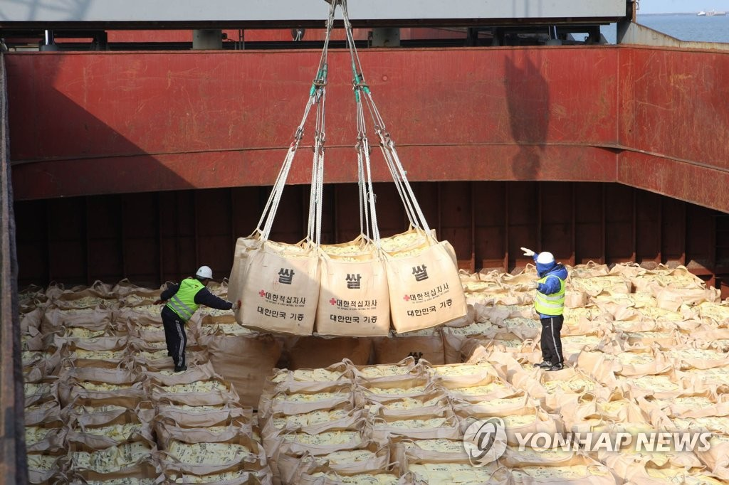 In this file photo, taken in 2010, workers load rice that will be sent to North Korea onto a ship in the southwestern port city of Gunsan. (Yonhap)