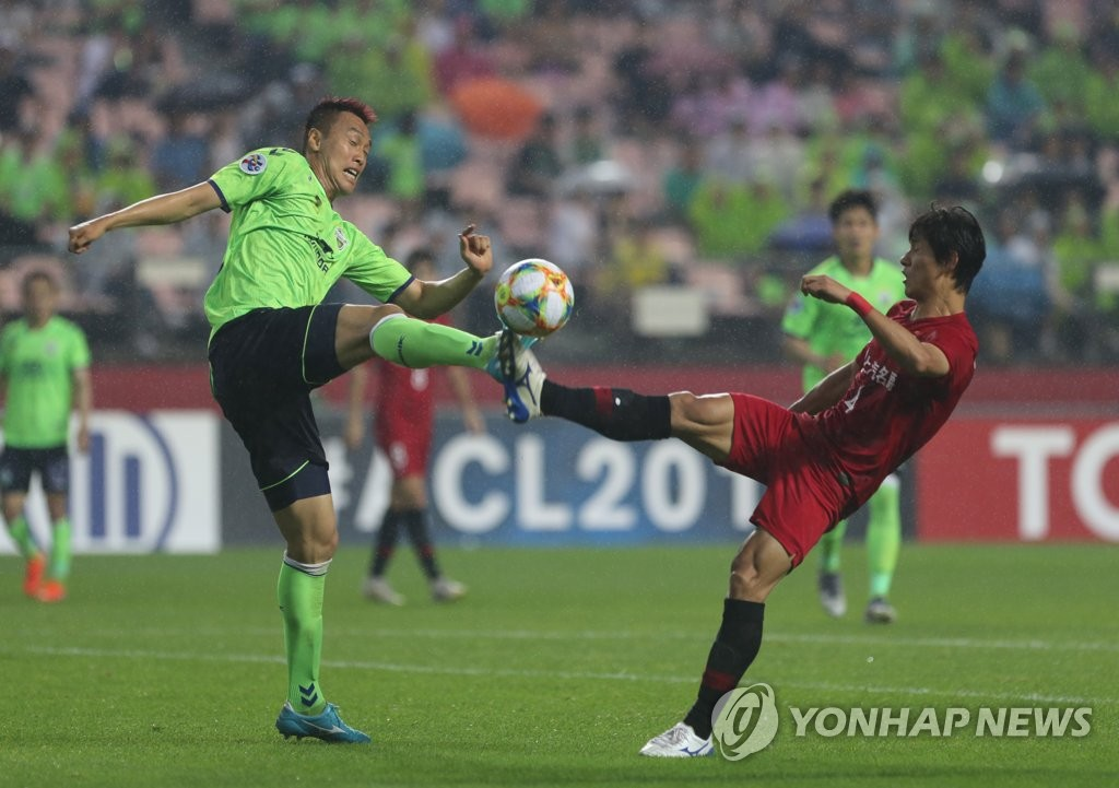 Kim Shin-wook of Jeonbuk Hyundai Motors (L) and Wang Shenchao of Shanghai SIPG battle for the ball during the second leg of the round of 16 at the Asian Football Confederation Champions League at Jeonju World Cup Stadium in Jeonju, 240 kilometers south of Seoul, on June 26, 2019. (Yonhap)