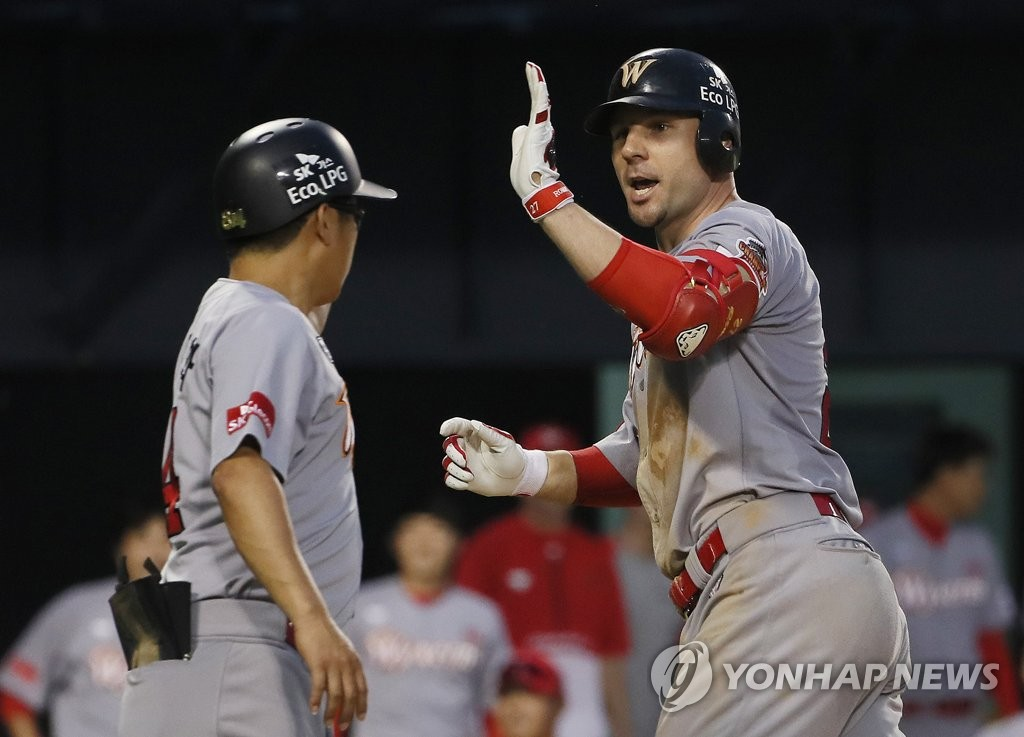 In this file photo from July 5, 2019, Jamie Romak of the SK Wyverns (R) high-fives his coach Cho Dong-hwa after hitting a two-run home run against the Doosan Bears in the top of the fifth inning of a Korea Baseball Organization regular season game at Jamsil Stadium in Seoul. (Yonhap)