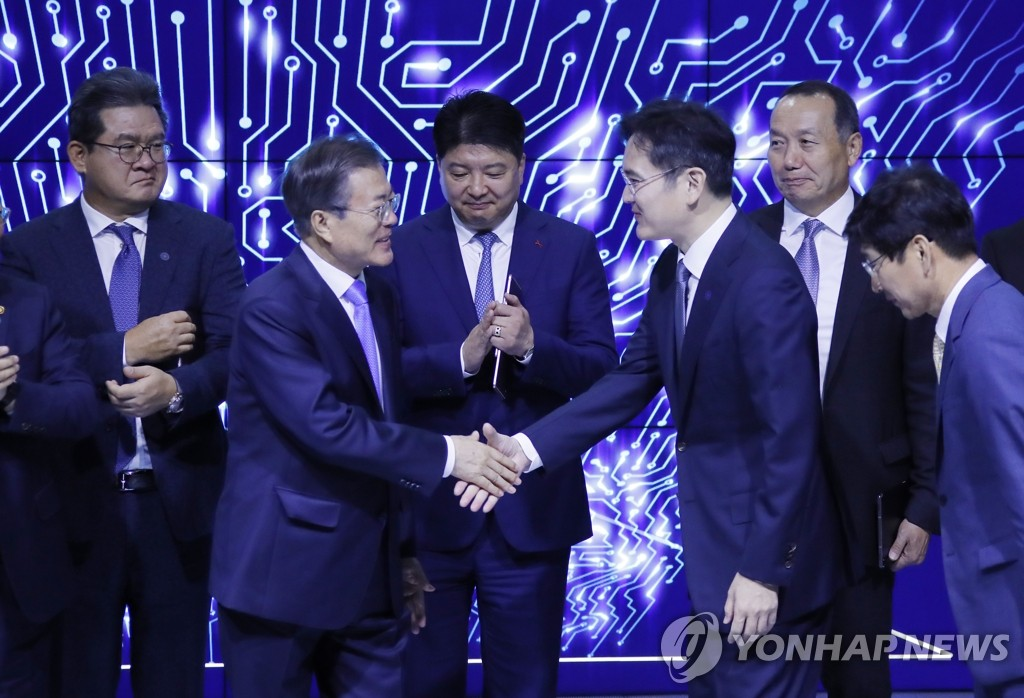 President Moon Jae-in (2nd from L) shakes hands with Samsung Group's leader, Lee Jae-yong, during an event held at Samsung Display's factory in Asan, South Chungcheong Province, on Oct. 10, 2019. (Yonhap)