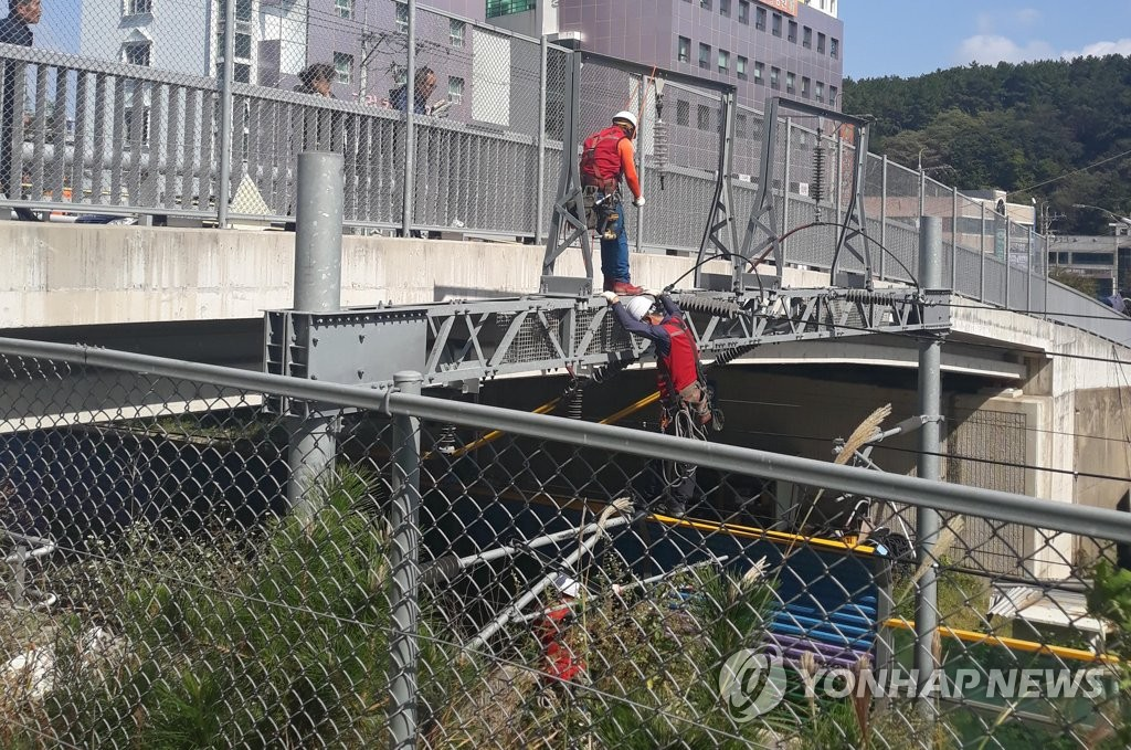 Technicians repair a railroad in the southern port city of Busan on Oct. 12, 2019, in this photo provided by Busan Fire Station, after a metal board fell on the railway amid Typhoon Hagibis, cutting off the power supply. (PHOTO NOT FOR SALE) (Yonhap)