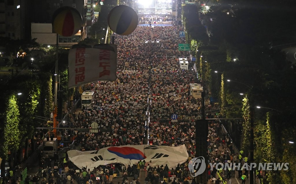 Supporters of Justice Minister Cho Kuk carry a huge national flag of South Korea, called the Taegeukgi, during a candlelight vigil in southern Seoul on Oct. 12, 2019. (Yonhap)