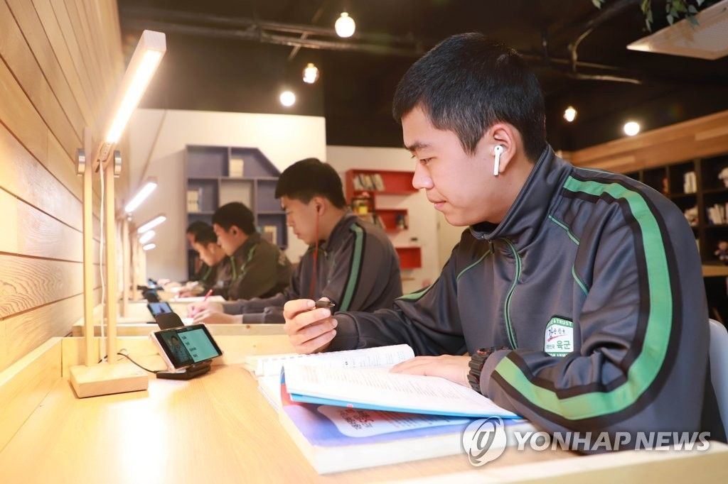 In this file photo, provided by the Army in October 2019, soldiers listen to internet lessons using their mobile phones at a military base in Yangju, north of Seoul, after the government allowed rank-and-file service members' mobile phone use on a trial run. (PHOTO NOT FOR SALE) (Yonhap)
