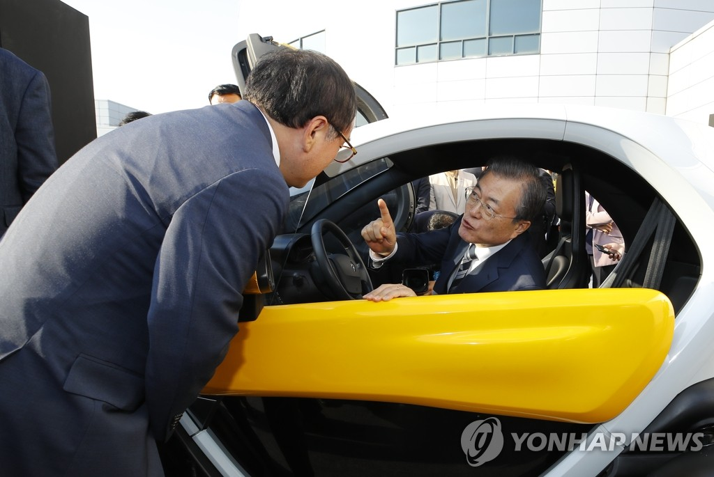 President Moon Jae-in talks with a Hyundai Motor official while in an electric vehicle at the firm's Namyang R&D Center in Hwaseong, Gyeonggi Province, on Oct. 15, 2019. (Yonhap)