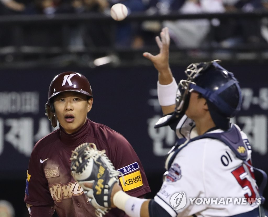 Song Sung-mun of the Kiwoom Heroes (L) watches as Doosan Bears' catcher Lee Heung-ryun grabs Song's bunt attempt in the top of the eighth inning of Game 2 of the Korean Series at Jamsil Stadium in Seoul on Oct. 23, 2019. (Yonhap)