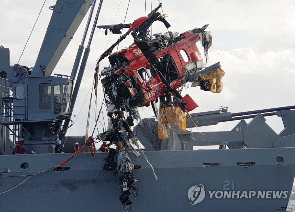 A destroyed rescue helicopter is salvaged from the waters in the East Sea by a Navy vessel on Nov. 3, 2019, four days after the crash that happened shortly after its takeoff from the easternmost islets of Dokdo, in this photo provided by the Donghae Coast Guard. Three victims have been found, with four others still missing. (PHOTO NOT FOR SALE) (Yonhap)