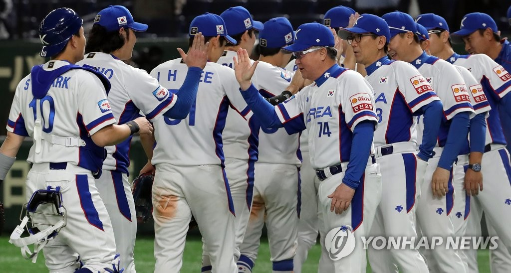 South Korean manager Kim Kyung-moon (C, No. 74) high-fives his players after their 5-1 win over the United States in the Super Round at the World Baseball Softball Confederation (WBSC) Premier12 at Tokyo Dome in Tokyo on Nov. 11, 2019. (Yonhap)