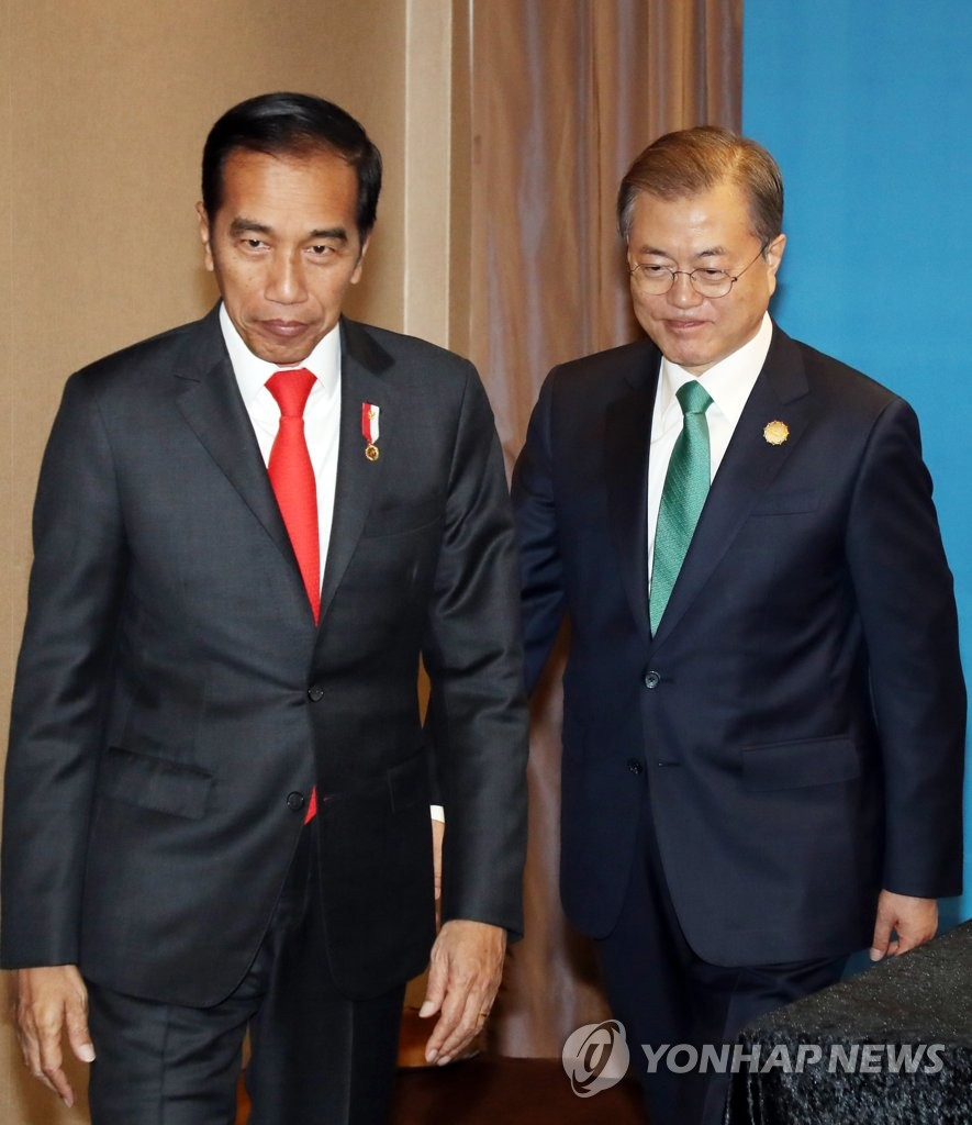 South Korea's President Moon Jae-in (R) and Indonesia's President Joko Widodo are seen here leaving their meeting on the sidelines of a special summit between South Korea and the Association of Southeast Asian Nations (ASEAN) in the port city of Busan, 450 kilometers southeast of Seoul, on Nov. 25, 2019. (Yonhap)