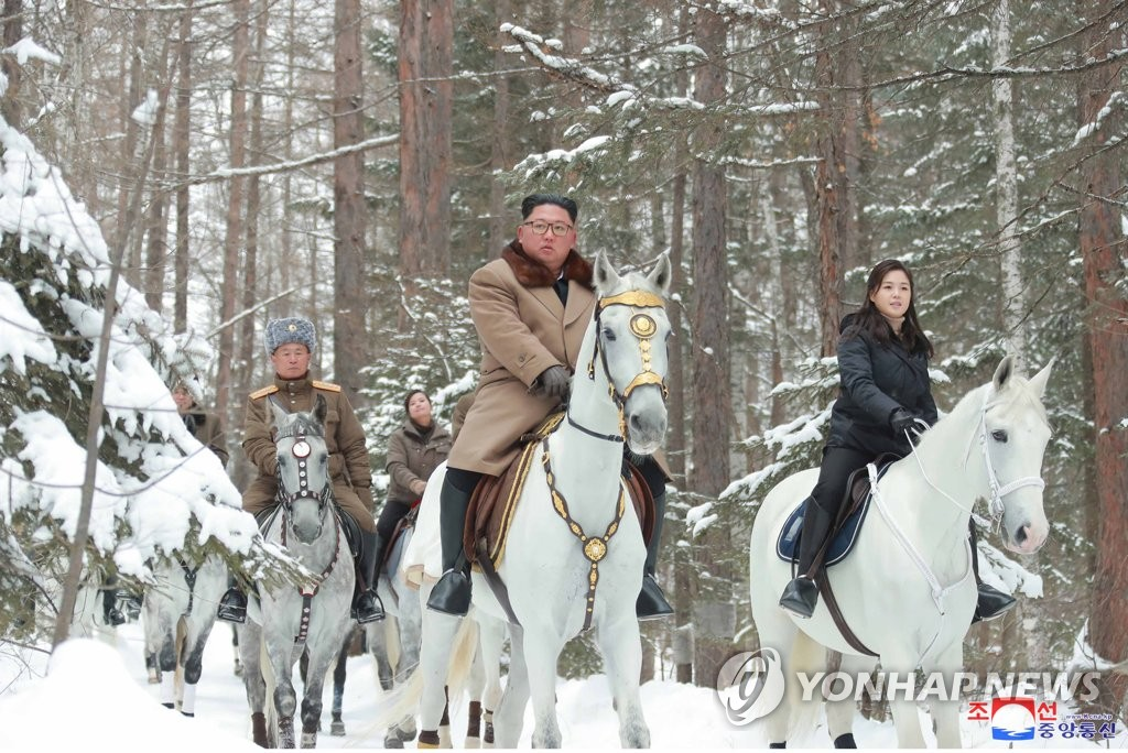 This photo, released by the Korean Central News Agency on Dec. 4, 2019, shows North Korean leader Kim Jong-un (C), alongside his wife, Ri Sol- ju (R), riding a white horse up a snow-covered Mount Paekdu, a volcano on the North Korean-Chinese border. Kim looked around revolutionary battle sites on the highest peak on the Korean Peninsula, considered sacred by Koreans. (For Use Only in the Republic of Korea. No Redistribution) (Yonhap)