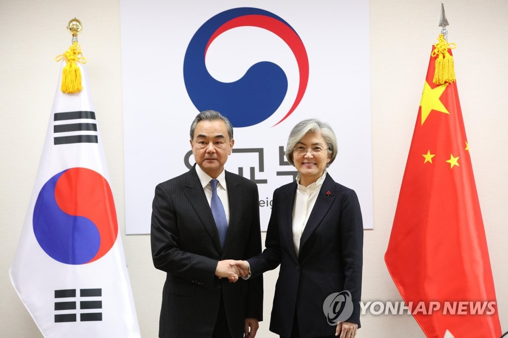 South Korean Foreign Minister Kang Kyung-wha (R) shakes hands with her Chinese counterpart, Wang Yi, before their talks at the foreign ministry in Seoul on Dec. 4, 2019. (Yonhap)