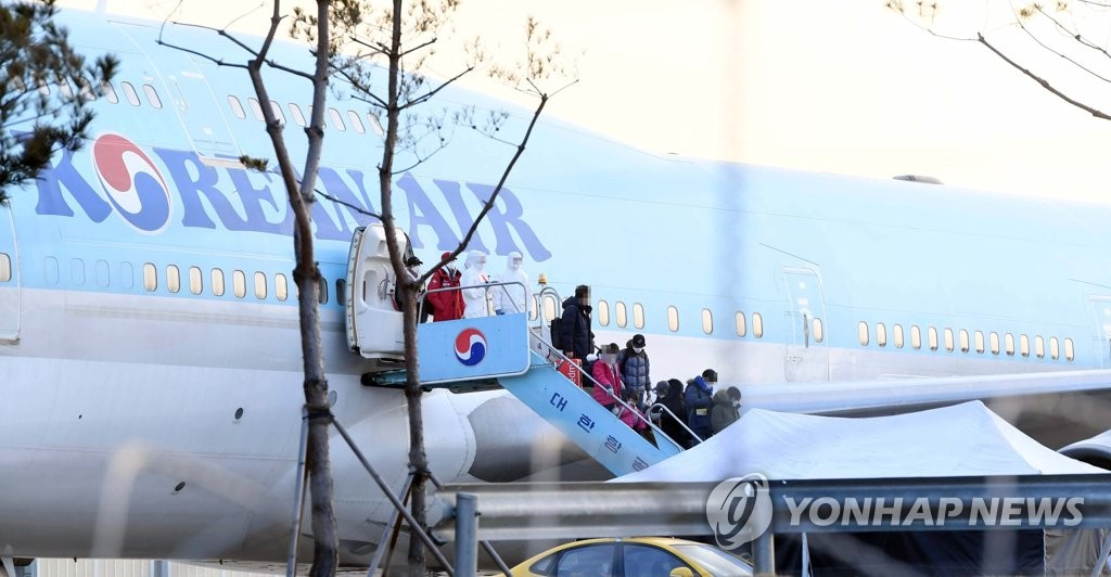South Korean evacuees from the coronavirus-hit Chinese city of Wuhan disembark from a chartered flight after arriving at Gimpo International Airport in Seoul on Jan. 31, 2020. South Korea's first evacuation plane brought back 368 nationals, and those with no symptoms were to be isolated at two state facilities for two weeks. (Yonhap)