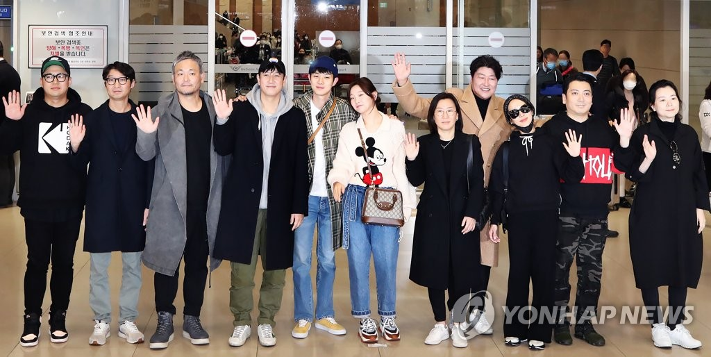 """Parasite"" cast and staff members pose for photos at Incheon International Airport, west of Seoul, on Feb. 12, 2020, returning from the 92nd Academy Awards in Los Angeles. (Yonhap)"