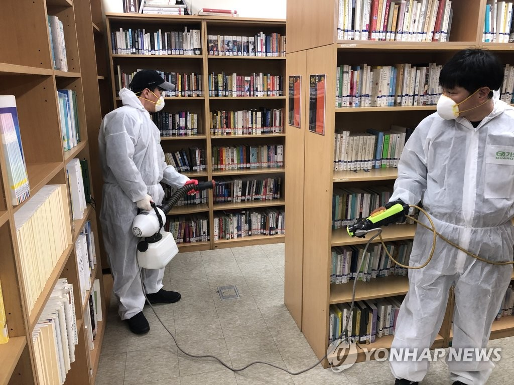 Quarantine workers in protective suits and masks disinfect a library in Seongdong Ward in Seoul on Feb. 16, 2020, in this photo provided by the ward office. (PHOTO NOT FOR SALE) (Yonhap)