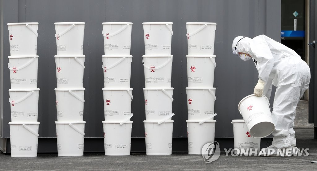 A worker carries a bucket of waste at a hospital in Daegu, 300 kilometers south of Seoul, on Feb. 29, 2020, as the city makes efforts to fight the spread of the new coronavirus. (Yonhap)