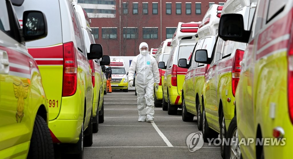 A health worker walks by ambulances in a parking lot in Daegu on March 1, 2020. (Yonhap)