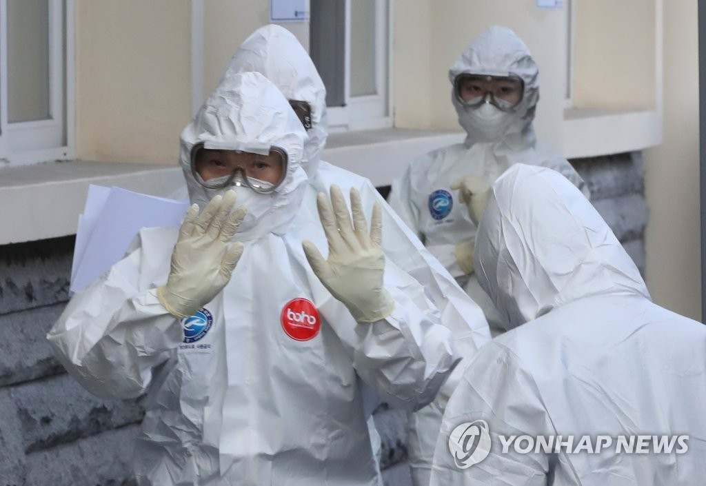 A medical worker wearing a full protective suit waves to a colleague as he enters a special ward to treat novel coronavirus patients at Keimyung University Dangsan Medical Center in Daegu, 300 kilometers southeast of Seoul, on March 5, 2020. (Yonhap)