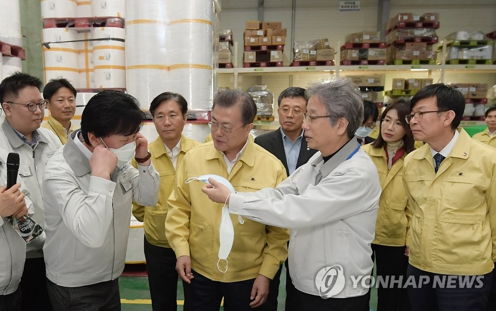 President Moon Jae-in (C) visits Wooil C&Tech Corp., a face mask-producing company in Pyeongtaek, south of Seoul, on March 6, 2020, and looks around its storage of mask materials. (Yonhap)