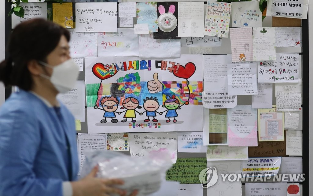 A medical staff member walks past a wall in a corridor at Dongsan Hospital in Daegu on March 9, 2020. The wall is decorated with various messages to cheer up virus patients and medical staff. (Yonhap)