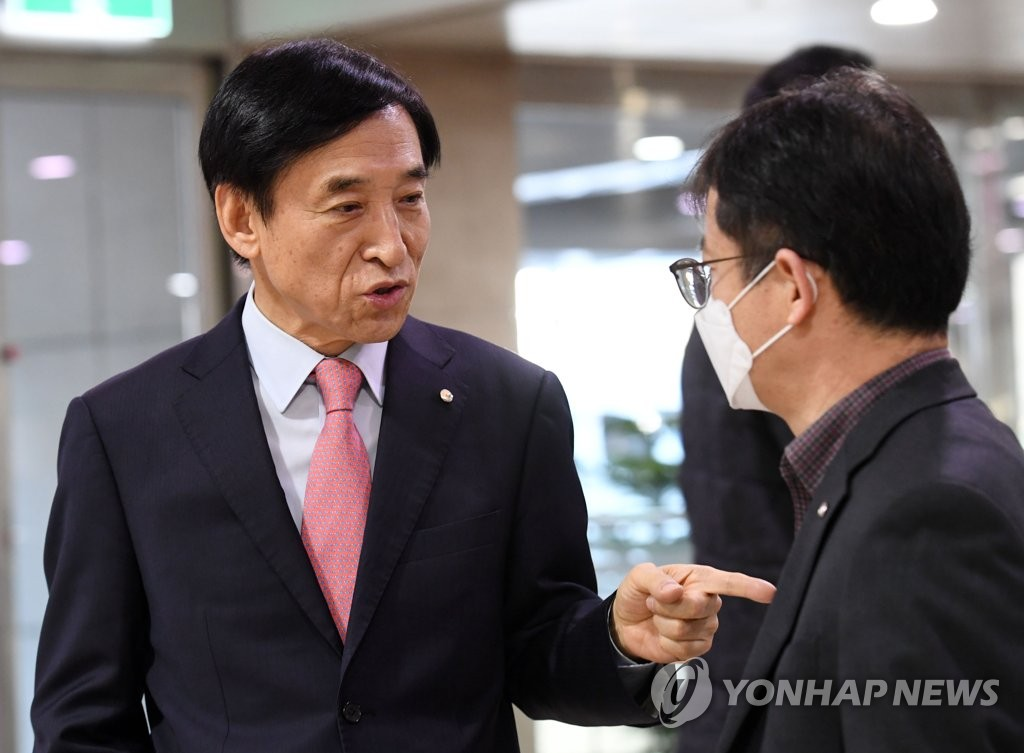 Bank of Korea (BOK) Gov. Lee Ju-yeol (L) speaks with a BOK official after meeting with journalists at the central bank building in Seoul on March 20, 2020. (Yonhap)