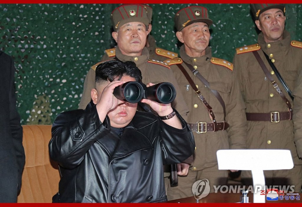 This photo released by the Korean Central News Agency on March 22, 2020, shows Kim Jong-un observe through binoculars a test of a newly-developed tactical weapon the previous day. (For Use Only in the Republic of Korea. No Redistribution) (Yonhap)