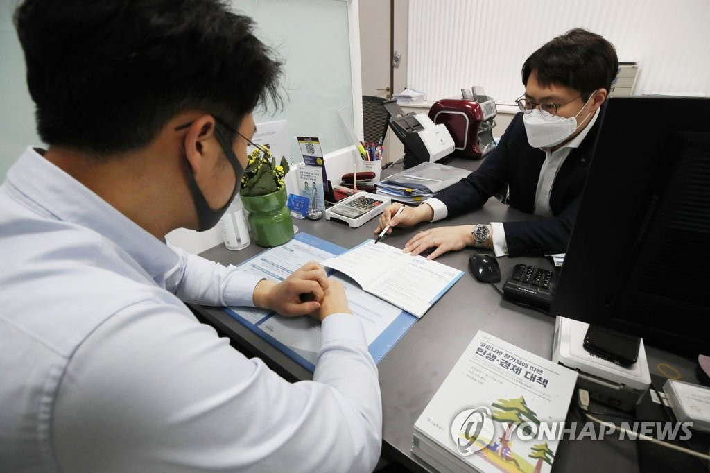 In the file photo, taken April 6, 2020, a bank official (R) interviews a customer applying for a special low-interest loan designed to help self-employed, small businesses hit by the new coronavirus outbreak at a Seoul bank. (Yonhap)