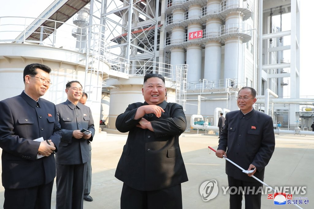 North Korean leader Kim (C) smiles while joining a fertilizer factory completion ceremony in this photo released by KCNA on May 2, 2020. This marked his first public appearance after 20 days of absence that sparked rumors about his health. (For Use Only in the Republic of Korea. No Redistribution) (Yonhap)