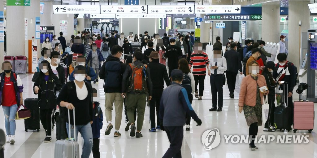 Travelers walk at Jeju International Airport in South Korea's southern resort island of Jeju on May 3, 2020. (Yonhap)