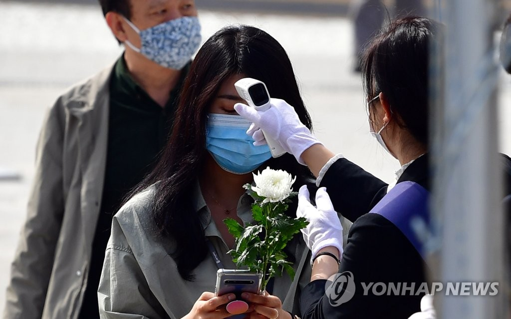 Visitors have their temperatures checked at a national cemetery honoring those killed in the 1980 democracy uprising in the southwestern city of Gwangju on May 18, 2020. (Yonhap)