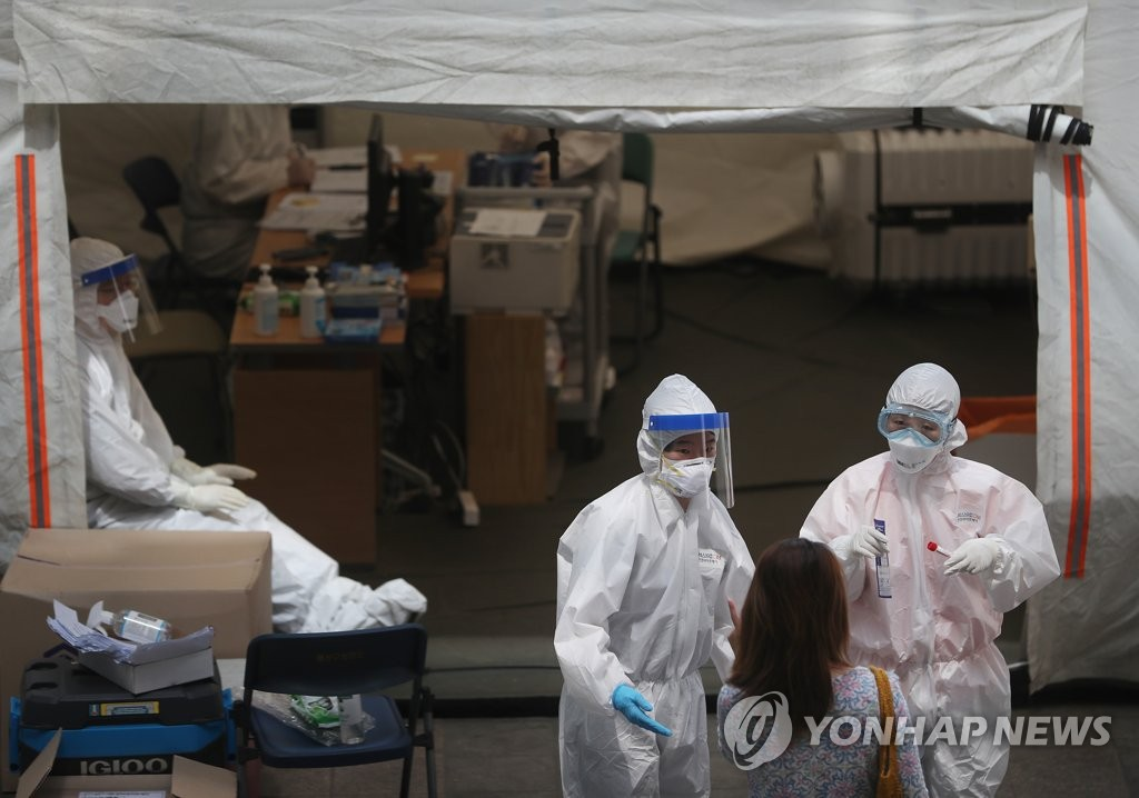 Medical workers carry out COVID-19 tests on visitors at a makeshift clinic in Seoul on May 18, 2020. (Yonhap)