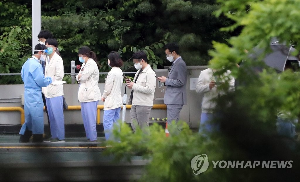 Hospital workers wait to get checked for the coronavirus at a screening center set up at the outdoor parking lot of Samsung Medical Center in the southern Seoul ward of Gangnam on May 19, 2020. (Yonhap)