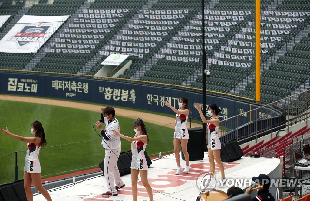In this file photo from May 31, 2020, cheerleaders for the Doosan Bears perform on a stage in front of empty seats at Jamsil Baseball Stadium in Seoul during a Korea Baseball Organization regular season game between the Bears and the Lotte Giants. (Yonhap)
