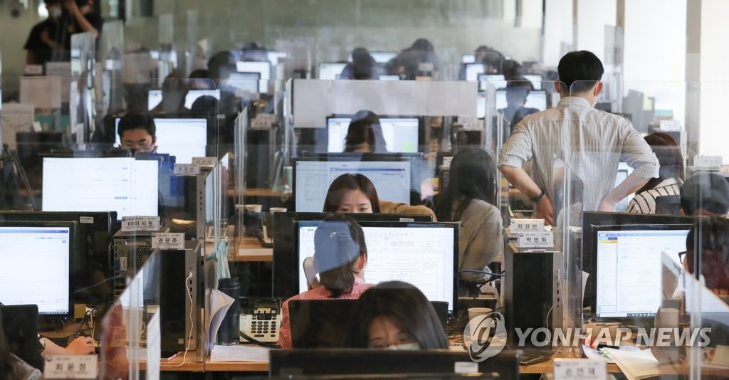 Employees work at desks with transparent partitions at an office located in central Seoul on June 3, 2020. (Yonhap)