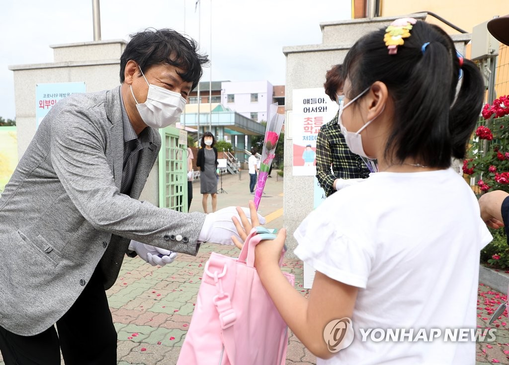 A teacher hands out flowers to welcome new students on their first day of school at an elementary school in Bucheon, west of Seoul, on June 11, 2020. (Yonhap)