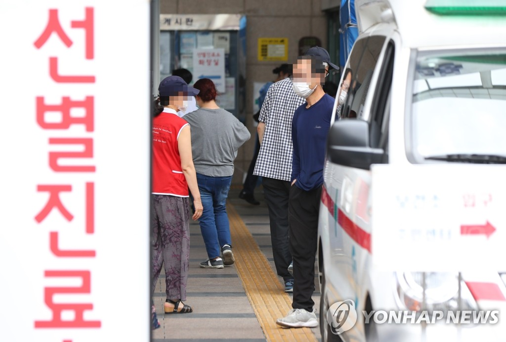 Visitors wait to take tests for the new coronavirus at a makeshift clinic located in nothern Seoul on June 12, 2020. (Yonhap)