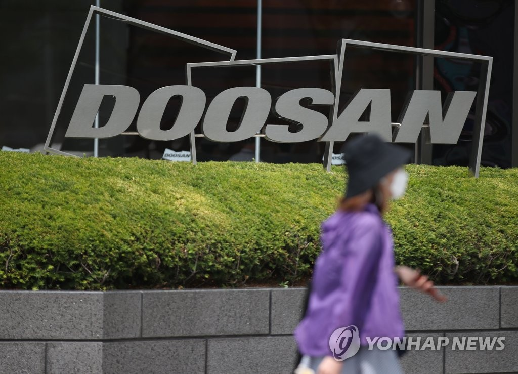 This photo shows a passerby walking past a logo of Doosan Group in front of the group's building in Seoul. (Yonhap)