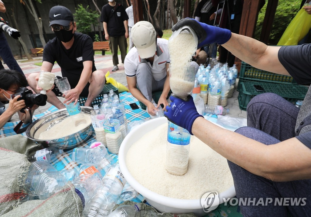 Defector activists put rice into PET bottles at a park in Seoul on June 18, 2020. They plan to drift them into North Korea via waters off the western island of Ganghwa bordering North Korea, despite the government's crackdown on their anti-Pyongyang activities, including the flying of balloons containing anti-Kim Jong-un leaflets into the North. (Yonhap)