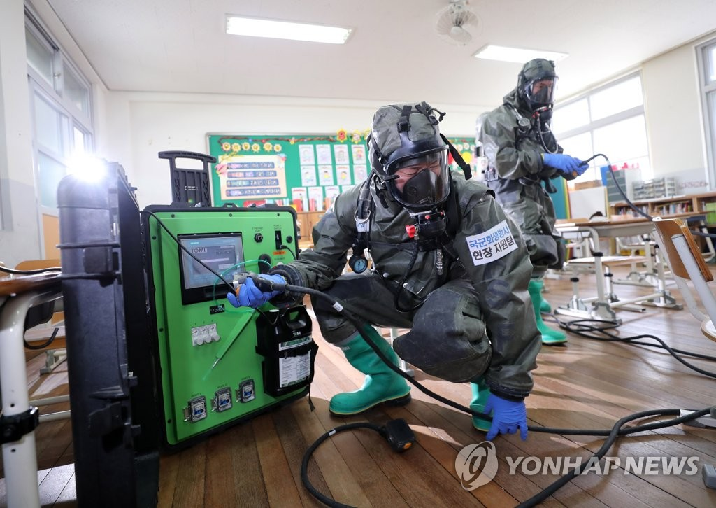 Military officials disinfect a classroom at an elementary school in Daejeon, 164 kilometers south of Seoul, on July 2, 2020. (Yonhap)