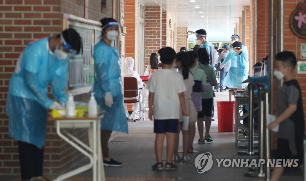 Students wait in line to receive new coronavirus tests at an elementary school located north of Seoul on July 5, 2020. (Yonhap)